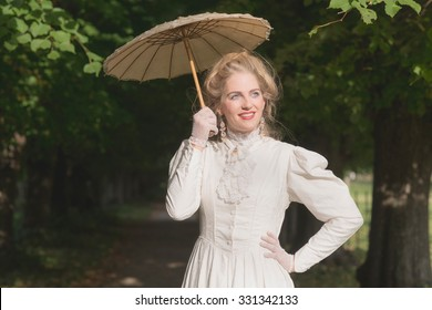 Posh victorian woman with parasol in garden.
