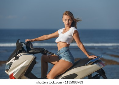 Posing on scooter, young pretty sexy girl outdoor portrait near ocean in sports wear, jeans, freedom, scooter, bike