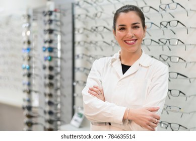 Posing optometrist woman in eyeglasses store smiling looking at camera. She is the owner.