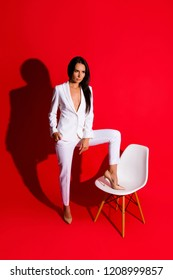 Posing snap portrait of skinny fit woman putting leg on chair looking away wearing white suit with sexual decollete isolated on bright red background. Photoshooting studio concept