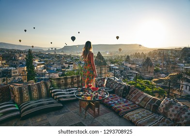 Posing at the terrace with the morning view of ballons, Cappadocia, Turkey