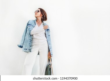 Posing woman in elegant white color outfit with oversize denim jacket