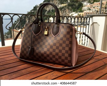 POSITANO, ITALY - APRIL 16, 2016: A Louis Vuitton handbag on a wood table on the balcony of a hotel in Positano, Italy.