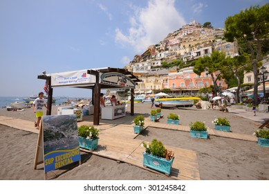 POSITANO ITALY - JULY 13, 2015 - A boy walks by a boat rental booth on the public beach in Positano