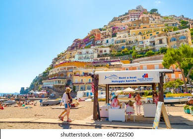 POSITANO, ITALY - JUNE 20, 2015: Sightseeing tourists visit boat rentals booth at travel destination Positano Beach on the Amalfi Coast of Italy