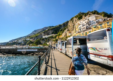 Positano, Italy - September 24 2017: A woman walks past a row of tourist busses parked along the Mediterranean sea at the village of Positano Italy