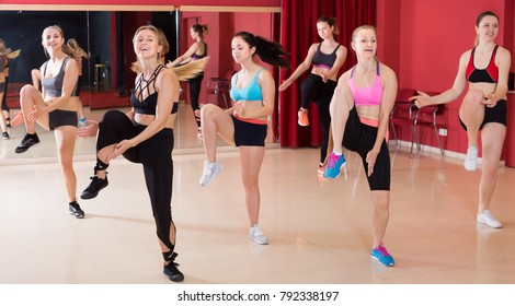 Positive active females funk jazz dancers exercising dance moves in studio