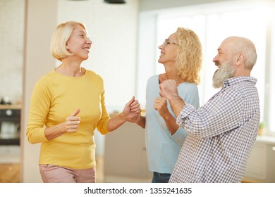 Positive active seniors in casual outfits dancing boogie-woogie in modern flat while having fun together on weekend