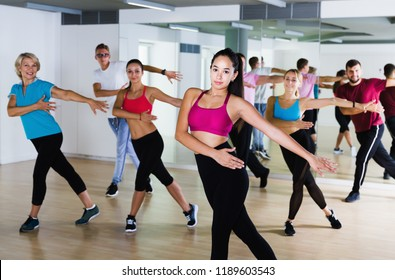 Positive active women and men of different ages dancing in  studio