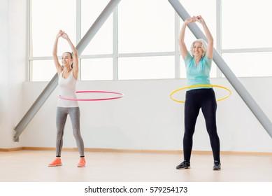 Positive active women rotating hula hoops