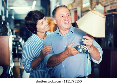 Positive adult female with husband are looking antique lamp in store