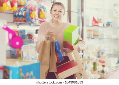 positive adult female standing in the children's store with toys, chair, pack and box