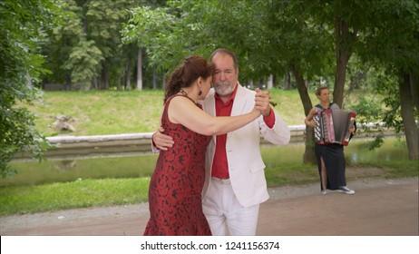 Positive adult friends dancing pair dance in garden. elderly couple dancing tango. Elderly man and woman dancing libertango.