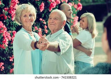 Positive  adult friends dancing pair dance in garden