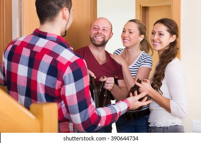Positive adult friends gathering together at house booze party