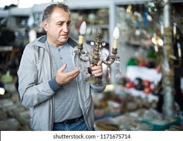 positive  adult male is choosing lamp at the market of old things.