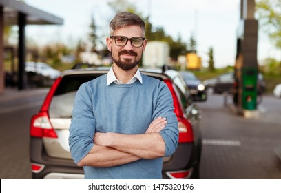 Positive adult man in casual outfit and glasses keeping arms crossed and looking at camera while standing on blurred background of car and gas station