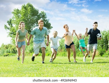 Positive adult parents with four children are being active and running in park on summer day