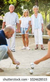 Positive adult people playing bocce in the garden