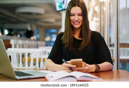 Positive adult woman sitting at modern cafe with laptop and messaging via smartphone while holding pen for writing ideas in notepad