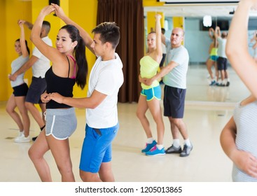 Positive adults dancing bachata together in dance studio