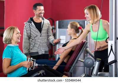 Positive adults of different age having strength training in gym
