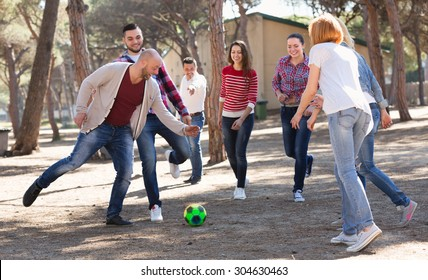 Positive adults friends chasing ball outdoors at sunny day