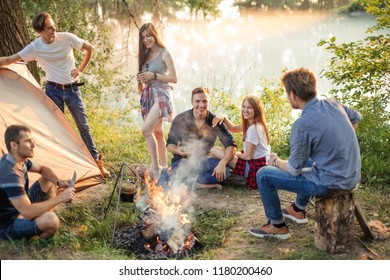 positive adventurous people are waiting for the preparation of dinner on the campfire