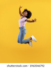 Positive african american bushy lady jumping and posing in mid-air, having fun over yellow studio background, crop. Summer vibe, joy and happiness concept. Full length shot