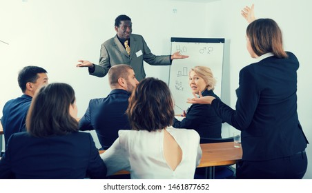 Positive African American business coach communicating with auditorium during training