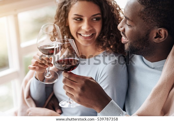 Positive African American couple holding wineglasses in the restaurant