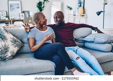 Positive african american couple in love sitting on comfortable couch having conversation about relationships,young dark skinned family resting at home together communicating at living room