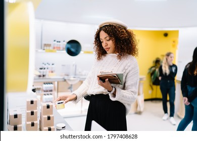 Positive African American female in casual clothes and beret standing in modern beauty shop and choosing goods during shopping with copybook in hand