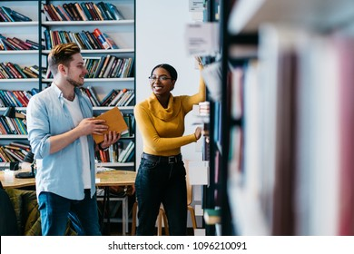 Positive african american female librarian helping caucasian student to search literature book in bookshelf.Cheerful two young people in casual wear discussing new bestseller standing in library