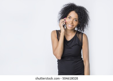 Positive African American girl is standing and talking on her phone against white background. Mockup