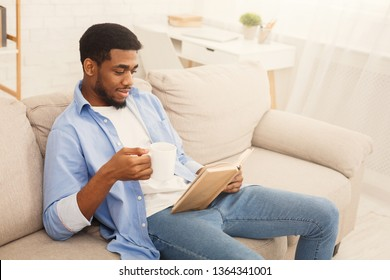 Positive african american guy reading book and enjoying cup of coffee at home, empty space