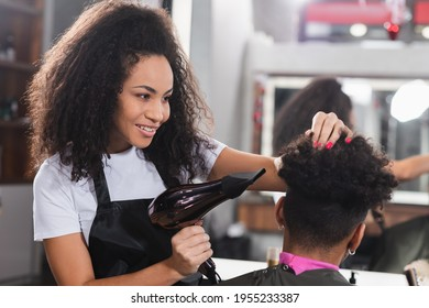 Positive african american hairdresser holding hair dryer near client on blurred foreground