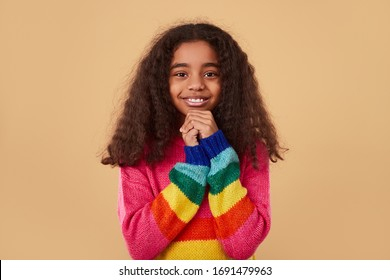 Positive African American little girl in colorful knitted sweater clasping hands and looking at camera with smile while making wish against beige background