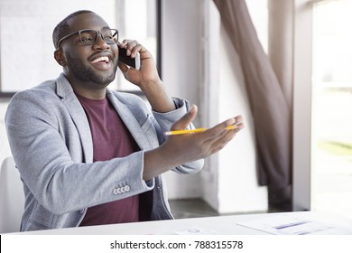 Positive African American male enterpreneur dressed in formal clothes, has conversation over smart phone, gestures actively with hand holds pencil, indicates at something as speaks with friend