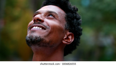 Positive african american man feeling hope and faith looking up