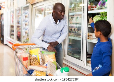 positive African American man with his little son making purchases together in grocery