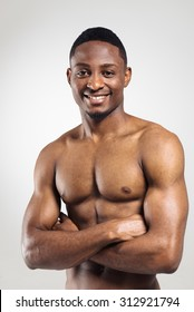 Positive african american muscular man with hands crossed on grey background