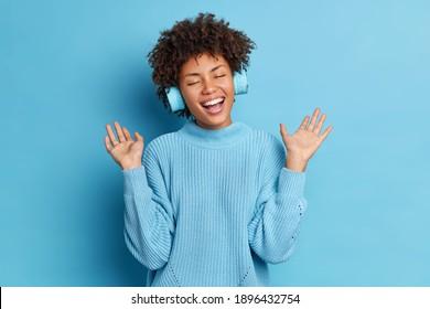 Positive Afroamerikanerin mit lockigen Haaren hebt Handflächen hat Spaß beim Hören der Audiospur trägt drahtlose Kopfhörer gekleidet in einem Gelegenheitsspringer einzeln auf blauem Hintergrund. Lieblingshobby