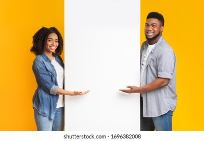 Positive African Couple Pointing At White Advertisement Board With Open Palms, Standing Together Over Yellow Background, Free Place For Your Text