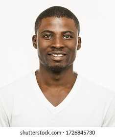 Positive Afro American man Smiles looking at camera. Portrait of dark-skinned cheerful man in white t-shirt isolated on white background. Front view.