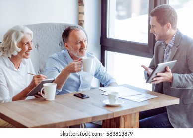 Positive aged couple meeting with sales manager
