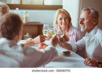 Positive aged couples drinking sparkling wine