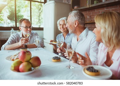 Positive aged friends having pleasant meal together at home