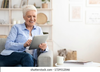 Positive Aged Lady Networking On Digital Tablet At Home, Relaxing On Sofa In Living Room, Enjoying Retirement, Copy Space