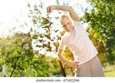 Positive aged man doing stretching exercises